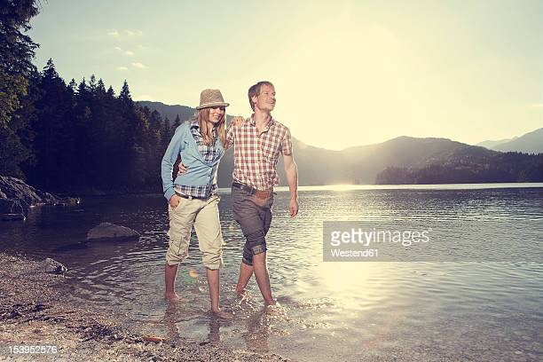 Germany, Bavaria, Couple walking in water, smiling