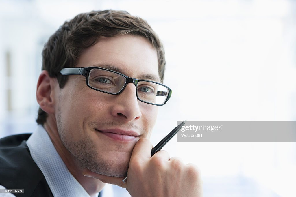 Germany, Bavaria, Diessen am Ammersee, Close up of businessman in thick spectacles holding pen, smiling, portrait