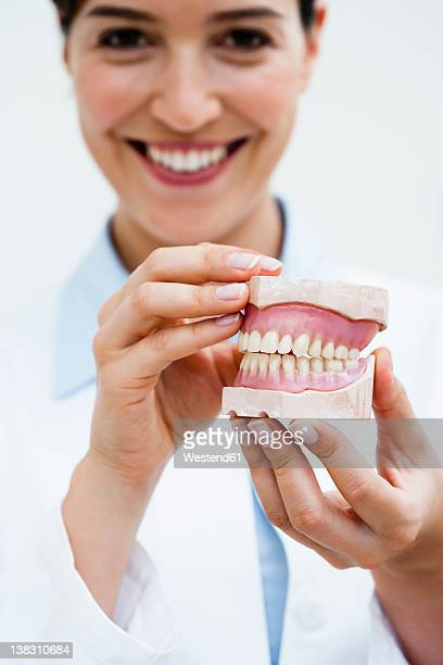 Germany, Bavaria, Diessen am Ammersee, Close up of young doctor exhibiting dentures, smiling