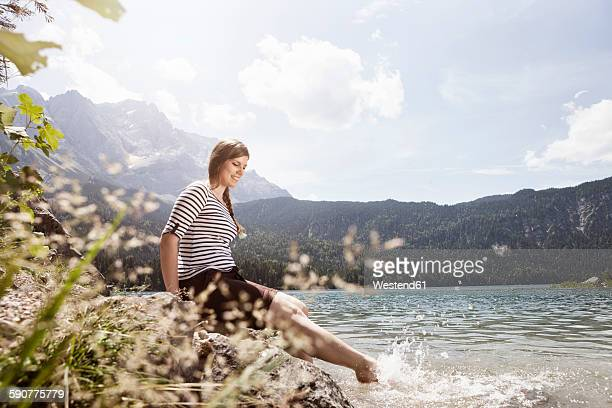 Germany, Bavaria, Eibsee, smiling woman splashing in water