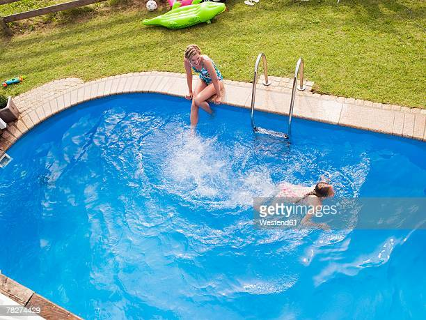 Germany, Bavaria,  mother watching daughter (10-11) swimming in pool, elevated view