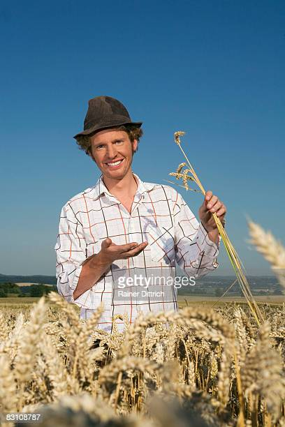 Germany, Bavaria, Farmer examining grains of wheat in field, smiling, portrait