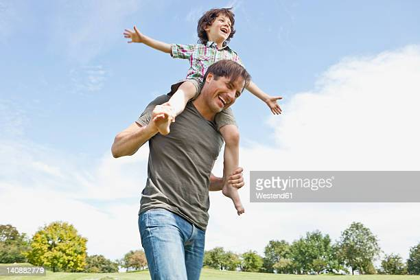 Germany, Bavaria, Father carrying son on shoulder in park, smiling