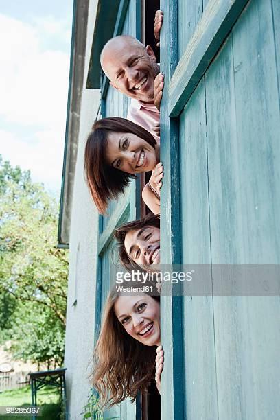 Germany, Bavaria, Four people at barn door, peeking