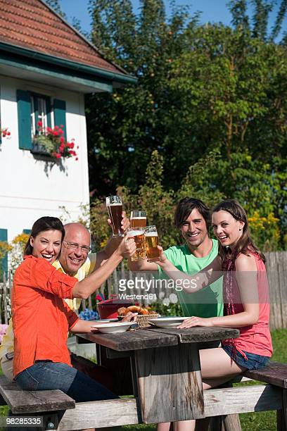 Germany, Bavaria, Friends sitting in garden, clinking beer glasses, smiling