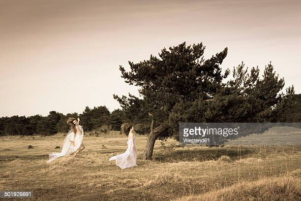 Germany, Bavaria, Froettmaning Heath, young women wearing a tulle dress and running and jumping