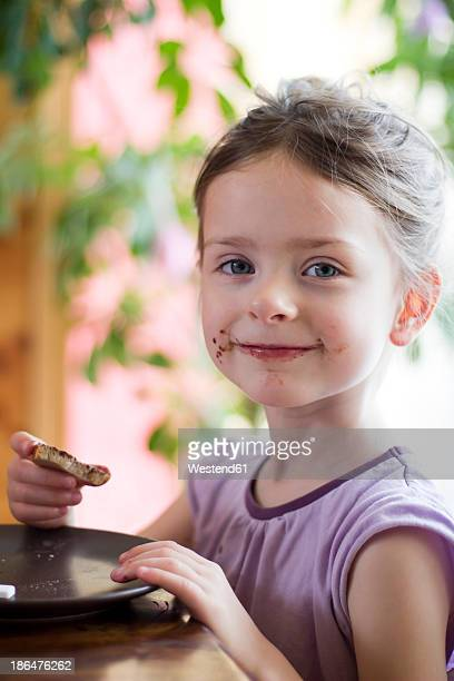 Germany, Bavaria, Girl eating toast with chocolate cream, portrait