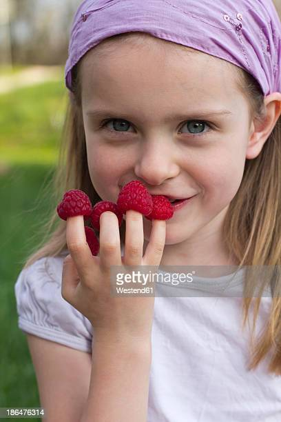 Germany, Bavaria, Girl holding raspberries on her finger