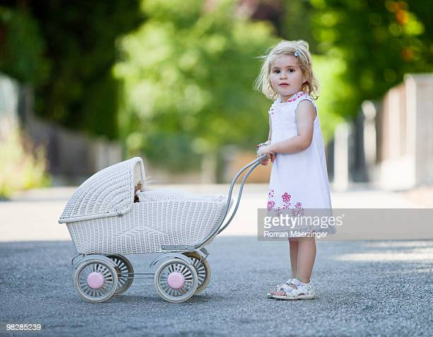 Germany, Bavaria, Girl (2-3) standing with holding pram