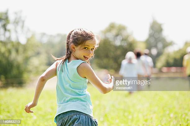 Germany, Bavaria, Girl running with family in background