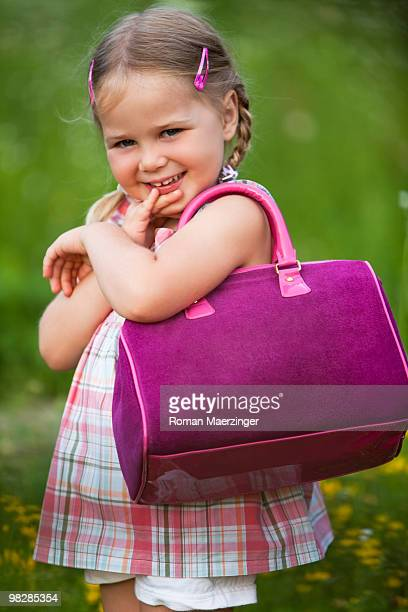 Germany, Bavaria, Girl (4-5) holding handbag, smiling, portrait