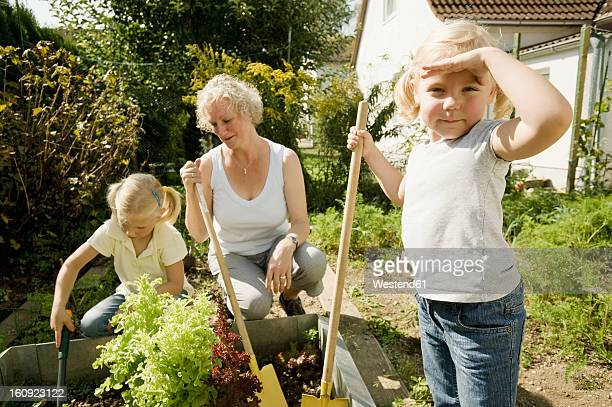 Germany, Bavaria, Grandmother with children working in vegetable garden