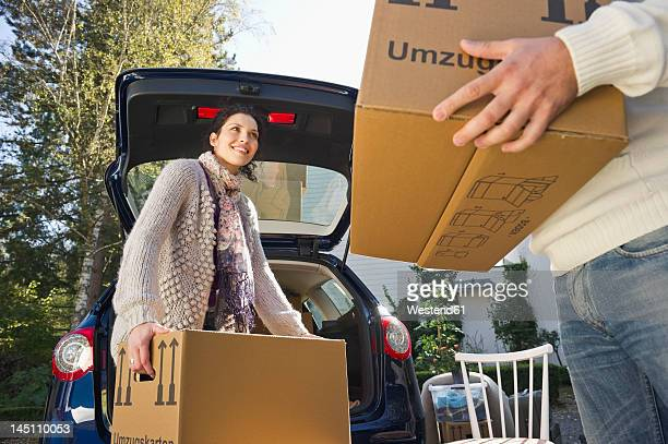Germany, Bavaria, Grobenzell, Couple loading boxes into car, smiling