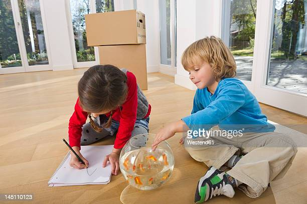 Germany, Bavaria, Grobenzell, Girl drawing and boy playing with goldfish bowl, smiling