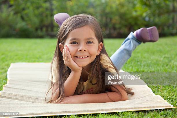 Germany, Bavaria, Huglfing, Girl lying in garden, smiling, portrait