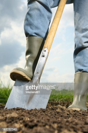 Germany, Bavaria, Human legs with spade on field