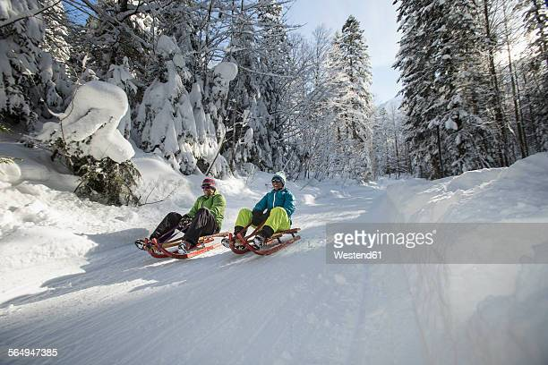 Germany, Bavaria, Inzell, couple having fun on sledges in snow-covered landscape