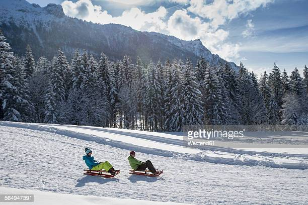 Germany, Bavaria, Inzell, couple on sledges in snow-covered landscape