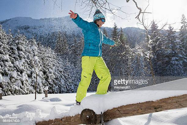 Germany, Bavaria, Inzell, woman balancing on snow-covered tree trunk