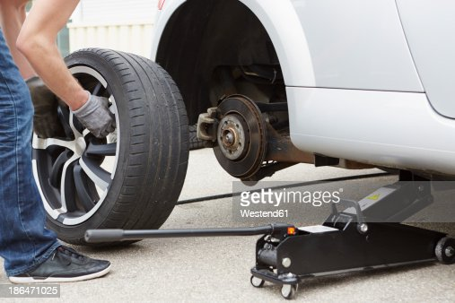 germany bavaria kaufbeuren mature man changing car tire stock photo getty images. Black Bedroom Furniture Sets. Home Design Ideas