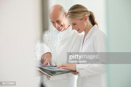 Germany, Bavaria, Landsberg, Dentist and female dental assistant holding documents, smiling : Foto de stock