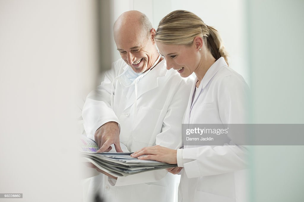 Germany, Bavaria, Landsberg, Dentist and female dental assistant holding documents, smiling : Stock Photo