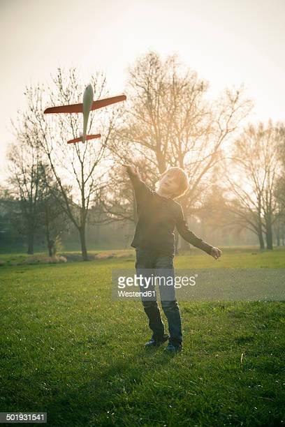 Germany, Bavaria, Landshut, Boy playing with toy aeroplane