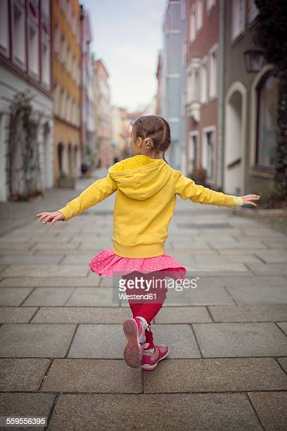 Germany, Bavaria, little girl dancing in an alley