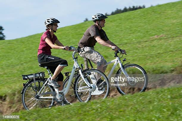 Germany, Bavaria, Man and woman riding electric bicycle