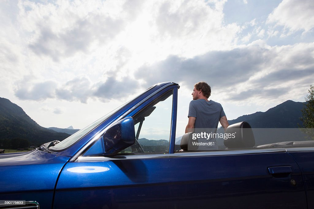 Germany, Bavaria, man next to convertible looking at view