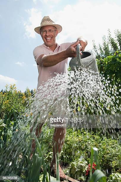 Germany, Bavaria, Mature man watering in garden, smiling