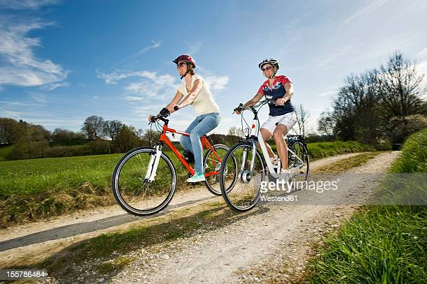 Germany, Bavaria, Mature woman riding electric bicycle