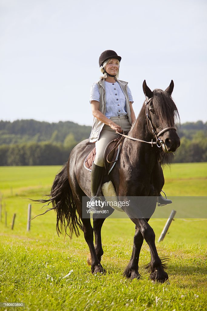 Germany, Bavaria, Mature woman riding horse