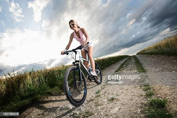 Germany, Bavaria, Mature woman riding mountain bike in grain field