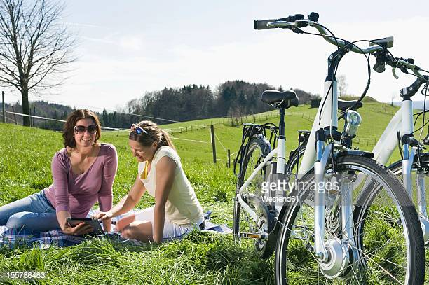 Germany, Bavaria, Mature women watching digital tablet, electric bicycle in foreground