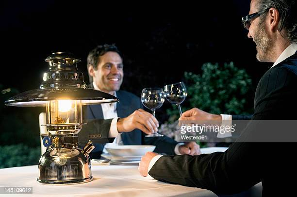 Germany, Bavaria, Men drinking wine at night