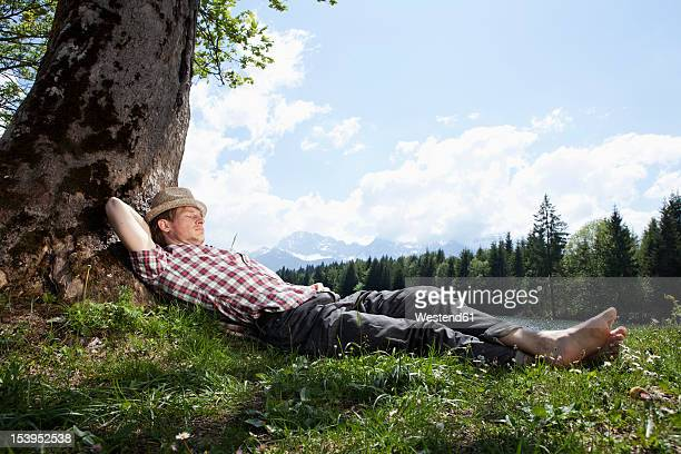 Germany, Bavaria, Mid adult man lying on grass under tree