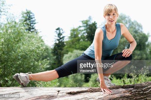 Germany, Bavaria, Mid adult woman exercising on tree stump, smiling, portrait