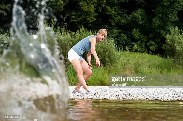 Germany, Bavaria, Mid adult woman having fun at Isar river