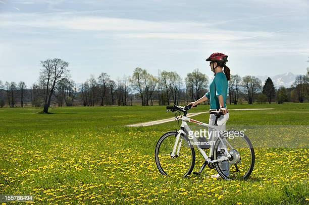 Germany, Bavaria, Mid adult woman riding electric bicycle