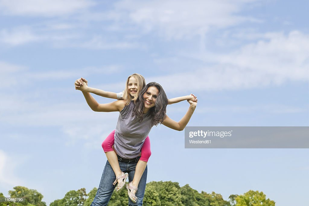 Germany, Bavaria, Mother giving piggy back ride to daughter in park, smiling, portrait : Stock Photo