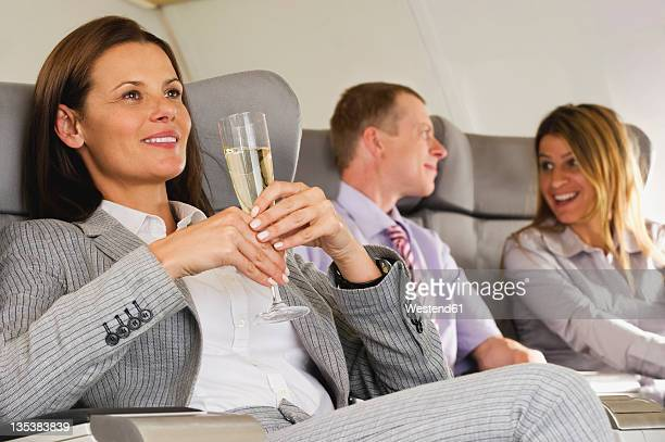 Germany, Bavaria, Munich, Business people talking and holding champagne in business class airplane cabin, smiling