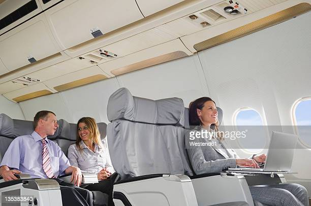 Germany, Bavaria, Munich, Business people talking and using laptop in business class airplane cabin, smiling