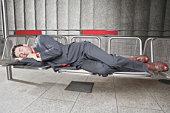 Germany, Bavaria, Munich, Businessman sleeping on bench at subway station