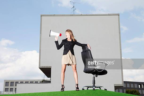 Germany, Bavaria, Munich, Businesswoman shouting through meghaphone in lawn