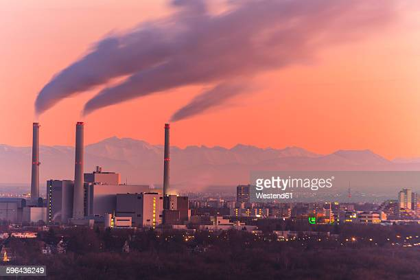 Germany, Bavaria, Munich, Cityscape at sunset with Alps in background