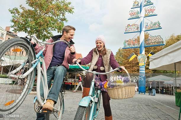 Germany, Bavaria, Munich, Couple cycling in Viktualienmarkt