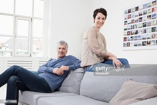 Germany, Bavaria, Munich, Couple sitting on sofa, smiling