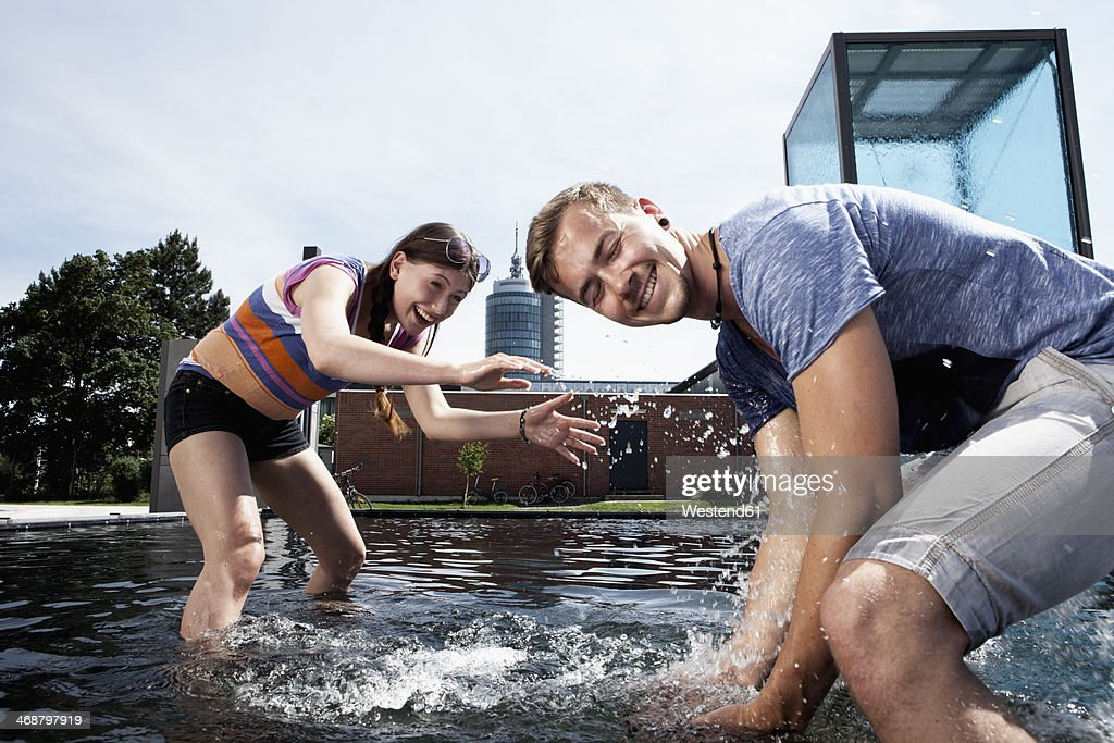 Germany, Bavaria, Munich, Couple splashing with water at fountain