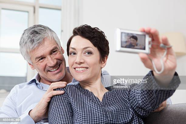 Germany, Bavaria, Munich, Couple taking self portrait of themselves at home, smiling